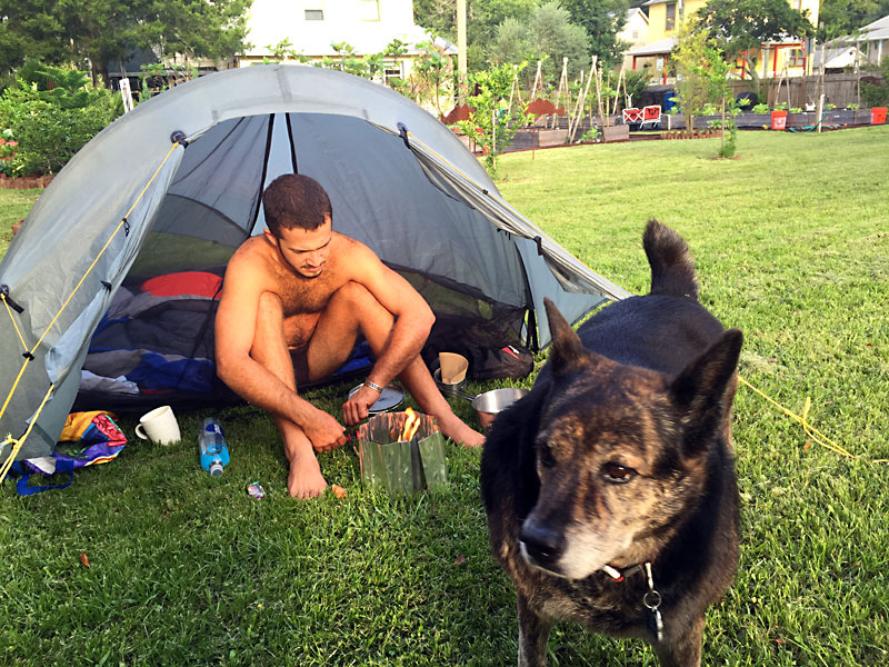 Alexander making coffee at Camp Ivanhoe while Ila Mae stands guard.