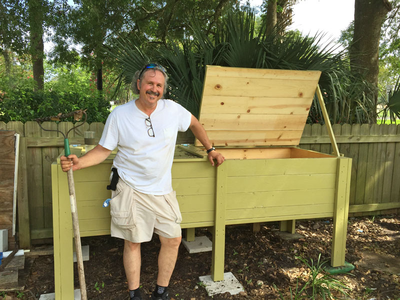 The After-Fifty Adventure Man standing beside his worm composting box. A Gentleman Farmer.